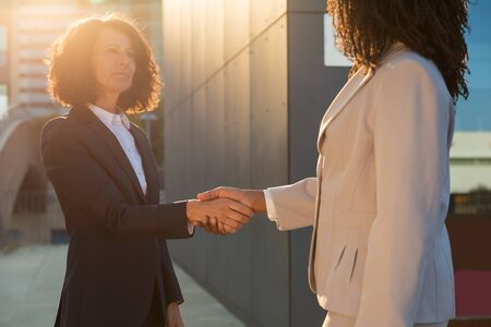 Female business colleagues meeting and greeting each other with handshake. Diverse business women in office clothing shaking hands outside. Businesswomen in city concept 写真素材