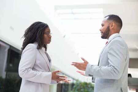 Serious confident business partners discussing project in office hall. Business man and woman standing and talking to each other. Business meeting or negotiation concept
