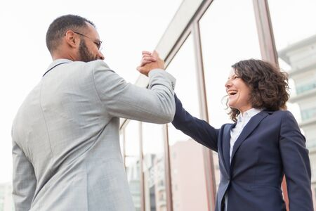 Business people giving high five. Low angle view of multiethnic businessman and businesswoman giving high five each other on street. Cooperation concept