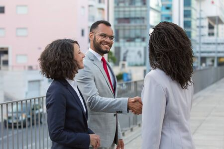 Cheerful satisfied partners finishing up meeting outside. Business man and women standing in city street, shaking hands, smiling and talking. Deal concept