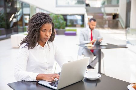 Focused hardworking female professional working on report during coffee break. Young African American business woman using laptop, man using tablet in background. Co-working concept