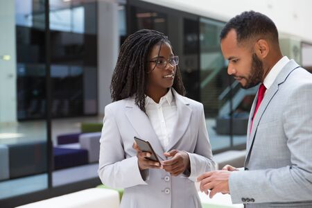 Excited business colleagues watching content on mobile phone together. Business woman showing smartphone screen to male colleague. Media content concept