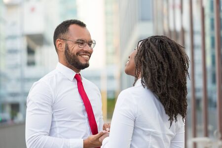 Happy diverse couple chatting outside. Business man and woman standing in city street, holding hands, smiling and talking. Corporate relationship concept