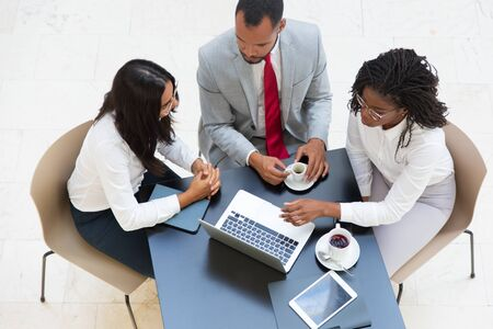 Business people watching and discussing project presentation while drinking coffee. Business man and women sitting at table with tablet and cups, working on laptop, looking at screen. Wi-Fi concept Stock Photo