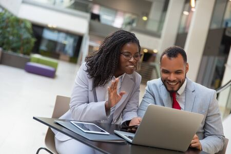 Cheerful coworkers using laptop. Smiling young African American business people sitting at table and using digital devices. Technology concept