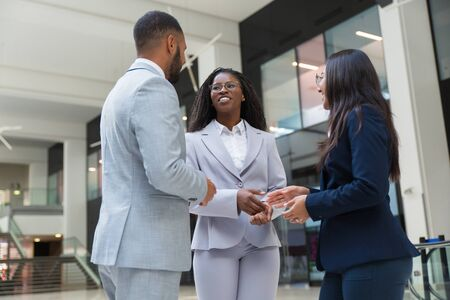 Happy diverse partners discussing deal in office hall. Business man and women standing in hallway, talking and laughing. Business communication concept