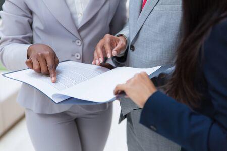 Cropped shot of business colleagues with papers. Mid section of business people standing together and looking at documents in folder. Teamwork concept