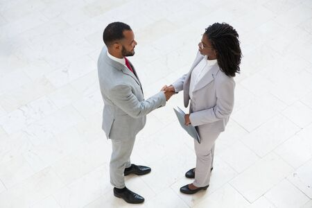 HR manager welcoming successful candidate in office hallway. Business man and woman standing and shaking hands. Hiring concept