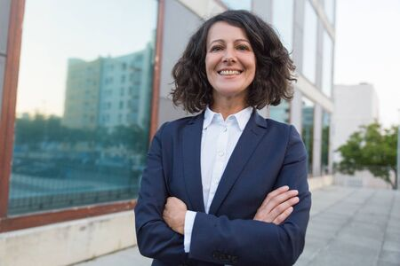 Confident middle aged businesswoman. Portrait of cheerful professional businesswoman in formal wear standing with crossed arms and smiling at camera. Business concept Stock Photo