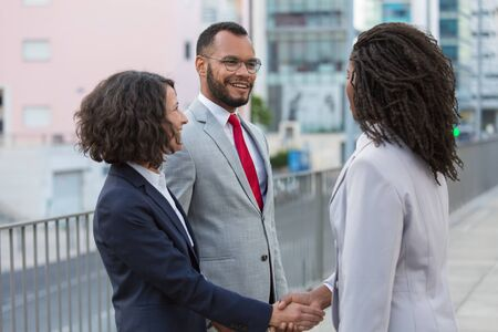 Friendly business partners discussing deal outside. Business man and women standing near city building, shaking hands, smiling and talking. Agreement concept