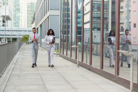 Serious young business people on street. Full length view of African American businessman and businesswoman with folder and digital tablet walking outside office building. Business concept Stock Photo