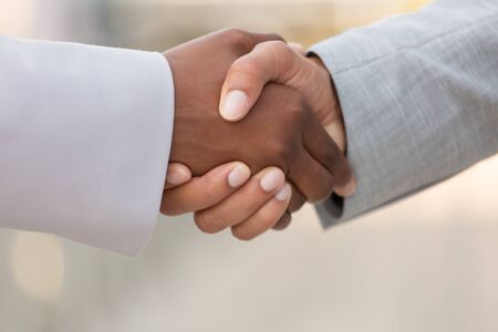 Closeup of multiethnic business colleagues handshake. Diverse business man and woman shaking hands. Collaboration concept