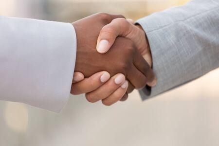 Primer plano de apretón de manos de colegas de negocios multiétnicos. Hombre de negocios diverso y mujer dándose la mano. Concepto de colaboración