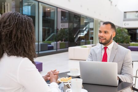 Positive excited businessman chatting with coworker over cup of coffee. Business man sitting at table opposite of his female colleague, smiling and using laptop. Business meeting concept