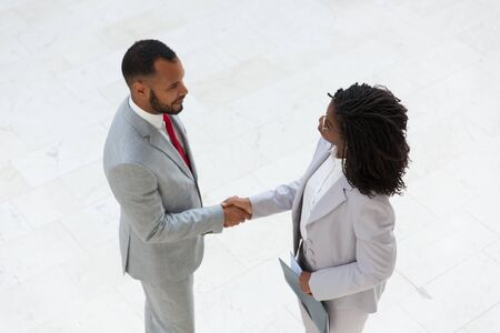 Business colleagues welcoming each other in office hallway. Business man and woman standing and shaking hands. Business meeting concept