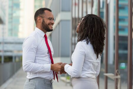 Cheerful multiethnic couple meeting outside during work break. Business man and woman standing in city street, holding hands, smiling and talking. Office dating concept