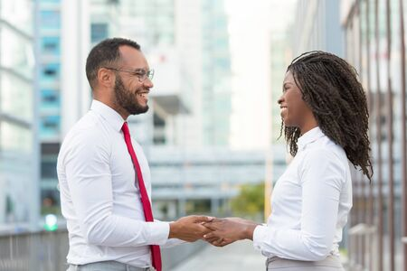 Happy friendly diverse colleagues sharing good news outside. Business man and woman standing in city street, holding hands, smiling and talking. Corporate friendship concept