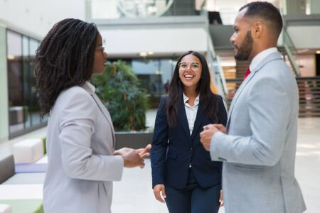 Happy confident businesswoman welcoming partners in office hall. Young business woman smiling and walking to diverse business couple. Meeting concept