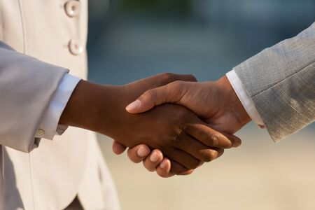 Dark skinned businesswoman shaking hands with male colleague. Closeup of business people handshake. Agreement concept Stock Photo