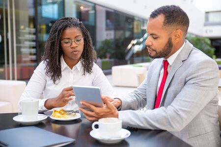 Diverse business colleagues watching project presentation on tablet. Business man and woman sitting in cafe, using tablet together and talking. Media content concept Stock Photo