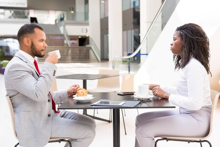 Diverse partners or colleagues meeting over cup of coffee. Side of business man and woman sitting at table in cafe, drinking coffee and talking. Business meeting or coffee hour concept
