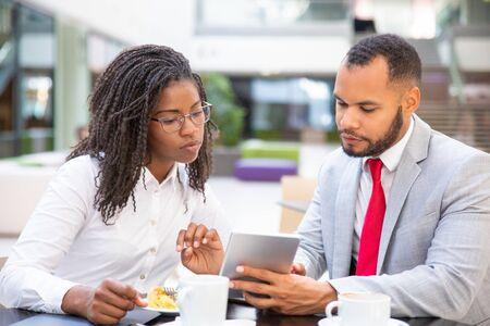 Des collègues de travail sérieux regardent ensemble du contenu sur une tablette. Divers homme et femme d'affaires assis dans un café, tenant une tablette et regardant l'écran. Concept de contenu multimédia Banque d'images