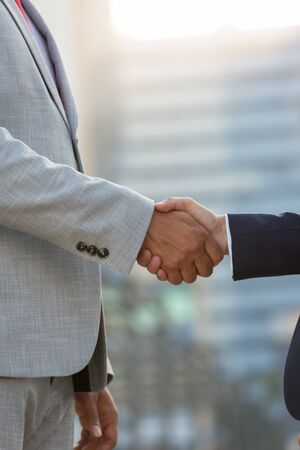 Businessman shaking hands with colleague in morning sunlight. Business man and woman in office suits meeting outside. Contract concept Stok Fotoğraf
