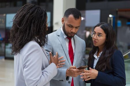 Serious coworkers using smartphone. Multiethnic young business colleagues standing together and using mobile phone. Communication concept