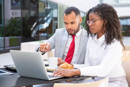 Serious coworkers watching and discussing presentation during breakfast. Business man and woman sitting in cafe outside and using laptop. Media content concept Stock Photo