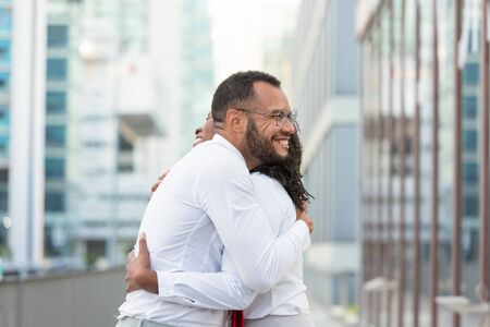 Joyful happy colleagues celebrating team success. Business man and woman standing in city street, smiling and hugging. Team success concept Stock Photo