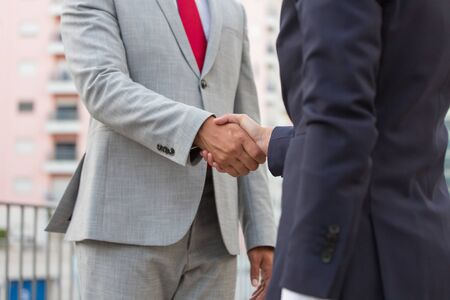 Business people shaking hands. Cropped shot of professional business people in formal wear shaking hands outdoor. Cooperation concept