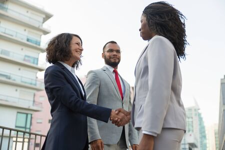 Group of diverse colleagues meeting outside. Business man and women standing near urban buildings and shaking hands. Successful cooperation concept Stock Photo