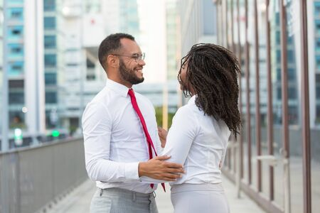 Happy old friends accidently meeting outside. Business man and woman standing in city street, hugging, smiling and talking. Old friends concept