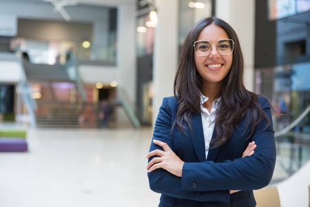 Young businesswoman smiling at camera. Portrait of cheerful Hispanic businesswoman in formal wear standing with crossed arms and looking at camera. Business concept Stock Photo