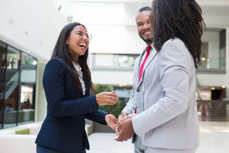 Joyful diverse business colleagues chatting during work break. Business man and women standing in office hall, talking and laughing. Corporate friendship concept