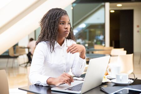 Serious female office employee using computer in coffee shop. African American business woman working on laptop in cafe and looking away. Wi-Fi concept