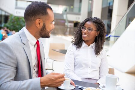 Friendly office colleagues enjoying coffee break together. Business man and woman sitting in cafe, drinking coffee, talking and smiling. Coffee hour concept