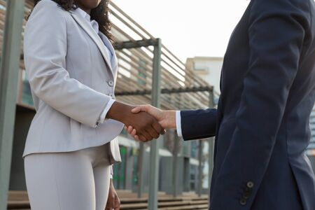 Successful businesswomen shaking hands outside. Female business colleagues meeting near office building. Communication concept Stock Photo