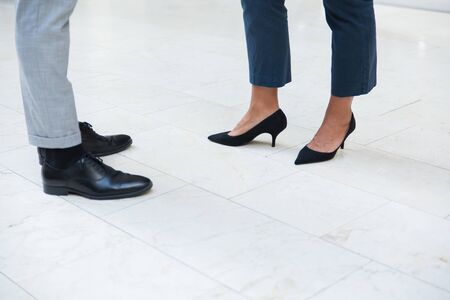 Two business people wearing office trousers and shoes standing on marble floor. Feet and ankles of business man and woman. Formal footwear concept Stock Photo