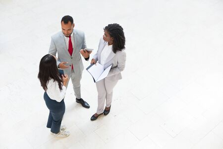 Diverse business team meeting in office hallway. Business man and women standing in circle, holding tablet and documents and talking. Teamwork concept Stock Photo
