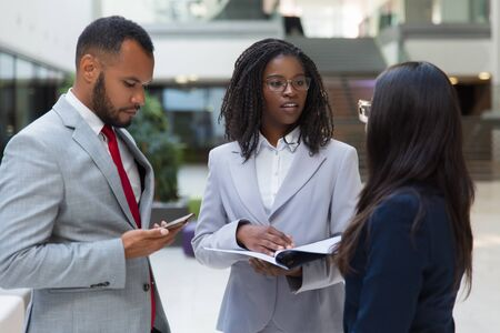 Successful diverse business people discussing contract in office hall. Business man and women standing in hallway, talking and reading document. Partnership concept Stock Photo