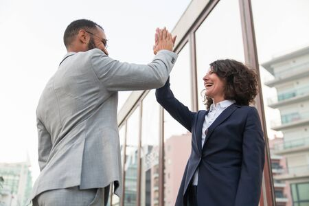 Cheerful business colleagues giving high five. Low angle view of multiethnic businessman and businesswoman giving high five each other on street. Cooperation concept Stock Photo