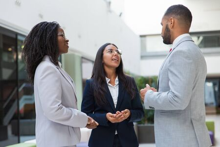Positive excited business partners discussing deal in office hall. Business man and women standing in hallway, talking, smiling. Negotiation concept Stock Photo