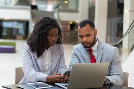 Serious business colleagues using gadgets. Young African American business people sitting at table and using digital devices. Technology concept Stock Photo