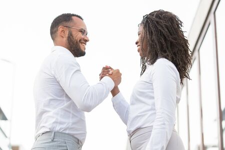Business team of two rejoicing at team success. Joyful business man and woman giving friendly handshake. Teamwork concept Stock Photo