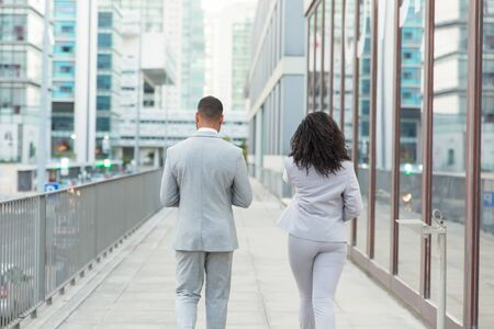 Back view of young business people on street. Rear view of African American businessman and businesswoman in formal wear walking together outside office building. Business concept Stock Photo