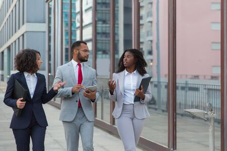 Coworkers walking and talking on street. Professional multiethnic business colleagues discussing work outside office building. Teamwork concept Stock Photo