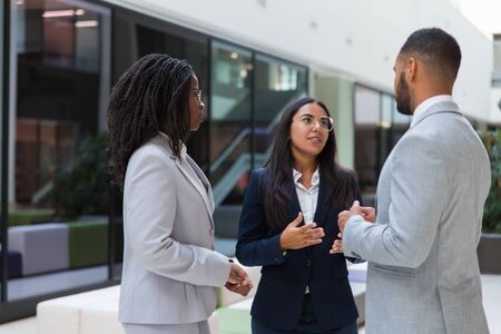 Confident female agent telling customers about project in office hall. Business man and women standing in hallway, talking and gesturing. Business meeting concept Stock Photo