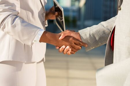 Dark skinned businesswoman holding tablet and shaking hands with male colleague. Closeup of business partners handshake. Digital device for business concept