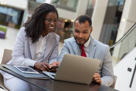 Cheerful business colleagues using laptop. Smiling young African American business people sitting at table and using digital devices. Technology concept Stock Photo